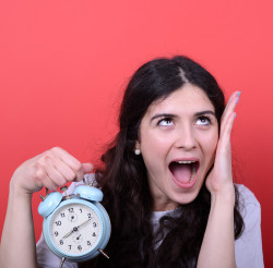 Portrait of girl screaming while holding clock against red background